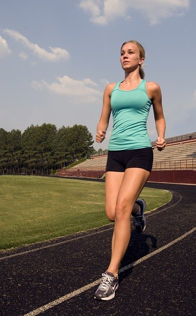 Woman running on a track with a green vest, black shorts, and Nike shoes